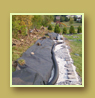Retaining wall under construction, drainage pipe and landscape fabric